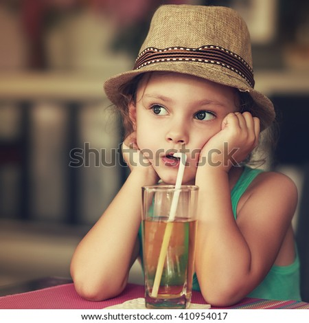 Cute kid girl in hat drinking apple juice in cafe and thinking about life with serious face. Vintage closeup portrait - stock photo