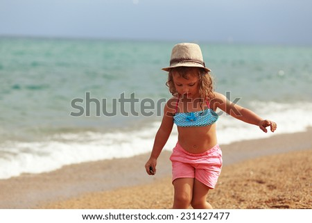 Cute kid girl in hat walking on the beach on the sand on sea background - stock photo
