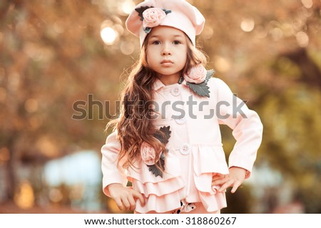 Cute kid girl 4-5 year old posing outdoors. Walking in park. Wearing stylish pink jacket. Looking at camera. Childhood.  - stock photo