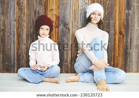 Cute kid girls of 7 and 12 years old wearing knitted trendy winter hats and sweaters posing over wood wall - stock photo