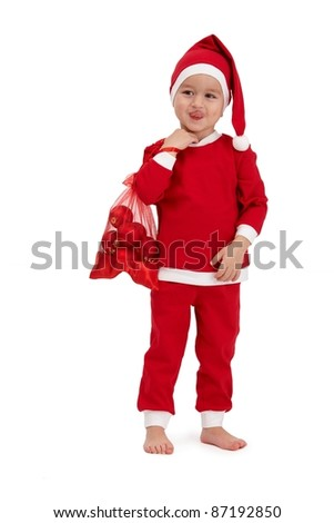 Cute kid grimacing in santa costume, sticking tongue, holding red bag.? - stock photo