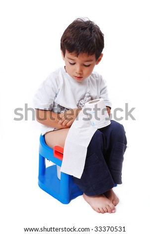 Cute kid is sitting on toilet and holding toilet paper - stock photo