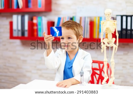 cute kid playing a doctor, looking at x-ray image of leg - stock photo