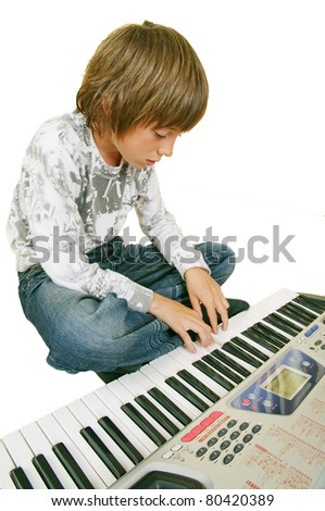 Cute kid playing piano, isolated on white background - stock photo