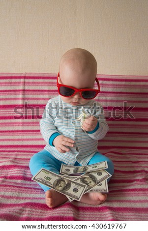 Cute kid playing with money - stock photo