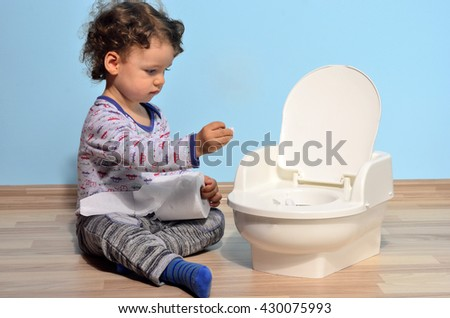 Cute kid potty training for pee and poo.Baby toddler sitting on the floor near a potty and playing with toilet paper - stock photo