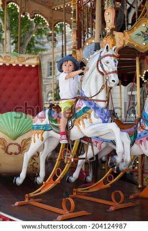 Cute kid, riding on a carousel, Europe - stock photo
