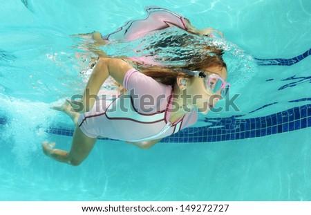 cute kid swimming underwater in pool - stock photo