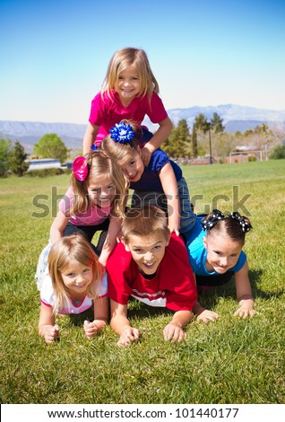 Cute Kids Building a Human Pyramid outdoors - stock photo