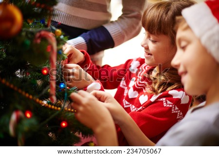 Cute kids decorating Christmas tree - stock photo