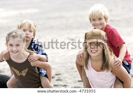 Cute kids giving piggy back rides at the beach - stock photo