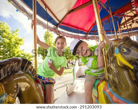 Cute kids having fun riding on a colorful carnival carousel - stock photo