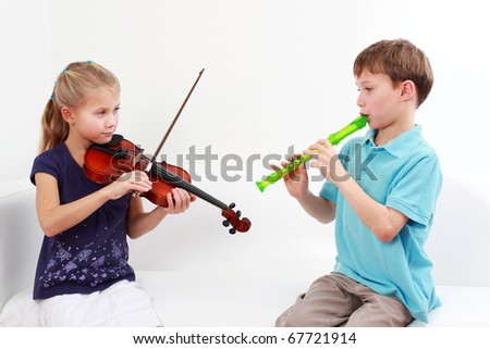 Cute kids playing flute and violin together - stock photo