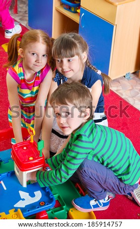Cute kids playing on the floor at kindergarten - stock photo