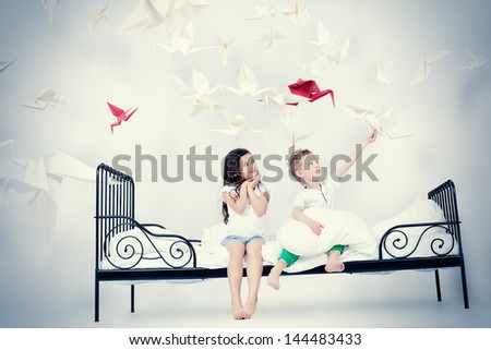 Cute kids sitting together on the bed under the blanket. Dream world. - stock photo