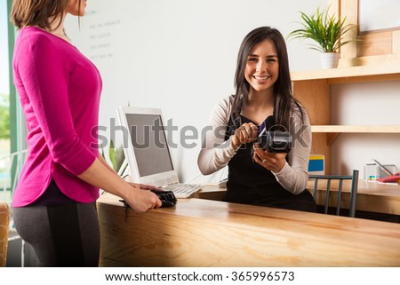 Cute Latin young woman working at a cash register and swiping the credit card of a customer - stock photo