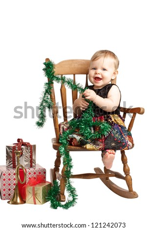 Cute laughing baby in velvet embroidered patchwork dress sits in rocking chair with festive holiday gifts and garland. Vertical, isolated/cut out on white background, copy space. - stock photo