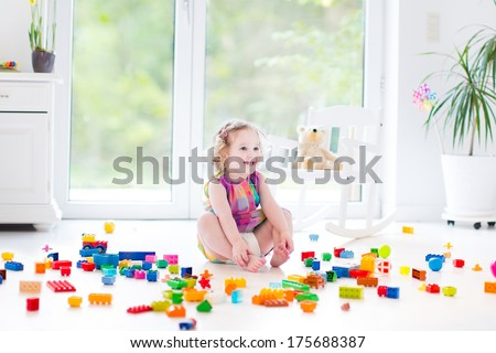 Cute laughing toddler girl playing with colorful blocks sitting on a floor in a sunny bedroom with a big window  - stock photo