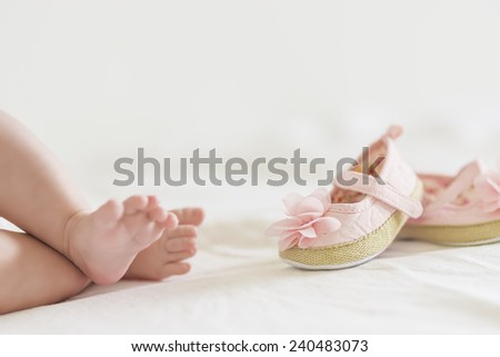 Cute Legs of Caucasian Newborn Child Against Bright Background. Horizontal Image Composition - stock photo