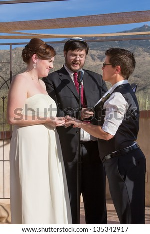 Cute lesbian couple in civil union with Jewish Rabbi - stock photo