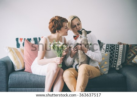 Cute lesbian couple in wedding outfits sitting with their cat. Gay marriage concept. Toned picture - stock photo