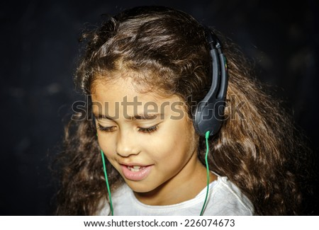 Cute little african-american girl listening music by headphones - stock photo