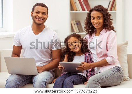 Cute little Afro-American girl and her beautiful young parents sitting on a sofa in the room. Father using a laptop, mother and daughter using a tablet. All looking at camera and smiling. - stock photo