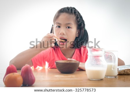 cute little Asian girl eating cereal with the milk on white background - stock photo