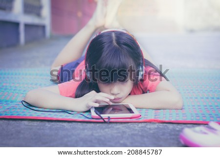 Cute little Asian girl is enjoying music using headphones  - stock photo