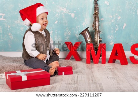 cute Little Baby boy in red santa hat with christmas presents sitting on the floor with Christmas decoration  - stock photo