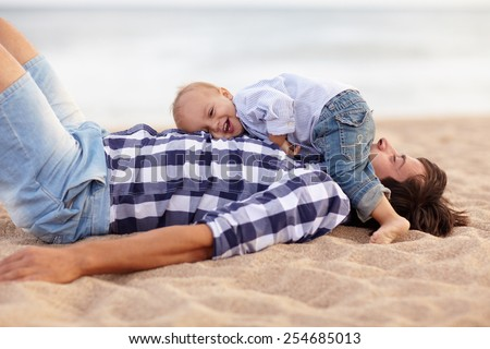 Cute little baby boy lying on his dad's chest and laughing out loud at the beach - stock photo