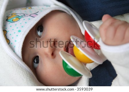 cute little baby boy lying with a colorful toy in his hand - stock photo