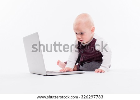 cute little baby boy sitting on a white background in front of a laptop and learns to type on it, photograph with depth of field - stock photo