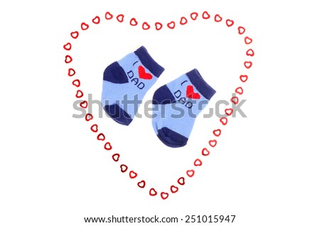 Cute little baby boy socks isolated on white. Small blue socks saying I love dad with heart. - stock photo