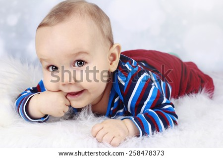 Cute little baby boy sucking his finger - stock photo