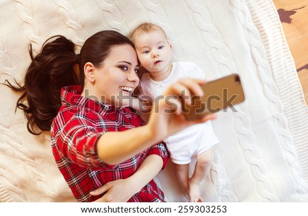 Cute little baby girl and her mother taking selfie on a blanket in a living room. - stock photo
