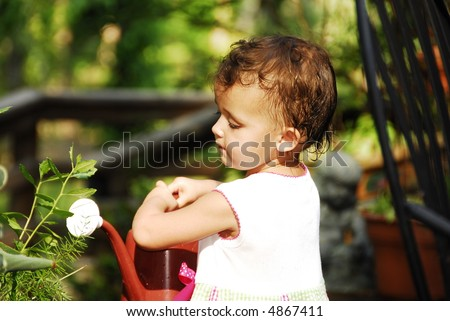 Cute little baby girl holding a watering can. - stock photo