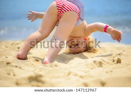 Cute little baby girl making yoga exercises at ocean beach - stock photo