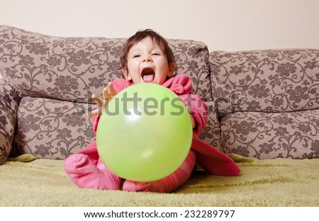 Cute little baby girl play with balloon at sofa - stock photo