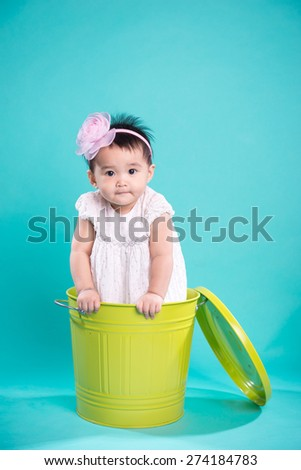 Cute little baby girl with brown eyes wearing a tutu and flower in her hair - stock photo