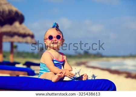 cute little baby girl with seashells on tropical sand beach - stock photo