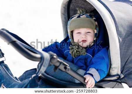 Cute little baby in a stroller outdoor in winter - stock photo