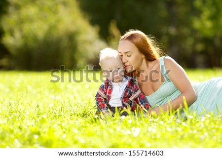 Cute little baby in summer  park with mother  on the grass. Sweet baby and mom  outdoors. Smiling emotional kid with mum on a walk. Smile of a child - stock photo