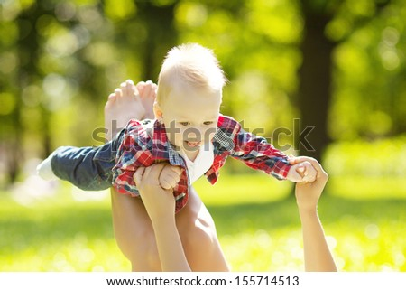 Cute little baby in the park with mother on the grass. Sweet baby and mom  outdoors. Smiling emotional kid with mum on a walk. Smile of a child - stock photo