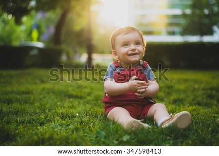Cute little baby laughing at the park. Real life shot of a baby - stock photo
