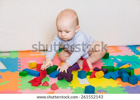 Cute little baby playing with colorful toys at home - stock photo