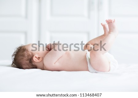 Cute little baby playing with its legs and sucking on its hand - stock photo