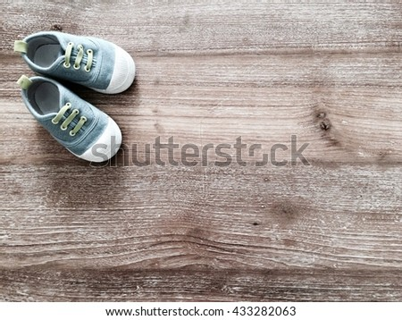 Cute little baby shoes on wood background , top view  - stock photo