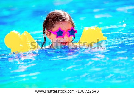 Cute little baby swimming in the pool, wearing funny sunglasses, enjoying summer weekend in aquapark, holidays and vacation concept - stock photo