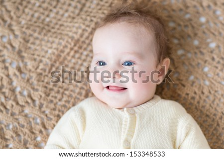 Cute little baby with beautiful blue eyes wearing a warm sweater playing on a brown knitted blanket - stock photo